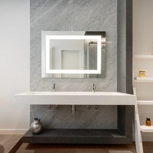 Esempio di una stanza da bagno padronale contemporanea di medie dimensioni con nessun'anta, piastrelle grigie, lastra di pietra, pareti bianche, parquet chiaro, lavabo sospeso, top in superficie solida, top bianco e pavimento marrone