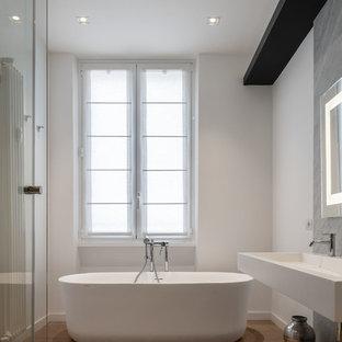 Foto di una stanza da bagno padronale minimal di medie dimensioni con nessun'anta, vasca freestanding, piastrelle grigie, lastra di pietra, pareti bianche, lavabo sospeso, top in superficie solida, top bianco e pavimento marrone