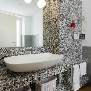 Foto di una stanza da bagno padronale contemporanea di medie dimensioni con nessun'anta, vasca da incasso, WC sospeso, pistrelle in bianco e nero, piastrelle a mosaico, pareti bianche, parquet chiaro, lavabo a bacinella, top piastrellato e pavimento beige