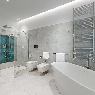 Esempio di una grande stanza da bagno con doccia contemporanea con ante lisce, vasca freestanding, doccia doppia, WC a due pezzi, piastrelle grigie, piastrelle in gres porcellanato, pareti grigie, pavimento in gres porcellanato, lavabo da incasso, pavimento grigio e porta doccia a battente