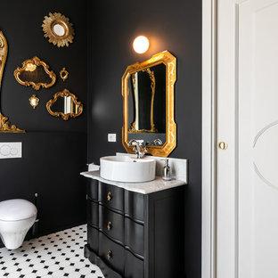 Aménagement d'une salle de bain principale éclectique avec des portes de placard noires, un WC suspendu, un mur noir et un sol en bois brun.