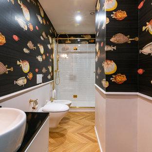 Réalisation d'une salle d'eau bohème avec des portes de placard blanches, un WC suspendu, un carrelage blanc, un mur noir et un sol en bois brun.