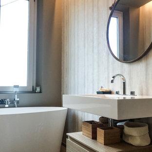 Ispirazione per una stanza da bagno padronale minimal di medie dimensioni con nessun'anta, ante beige, vasca freestanding, piastrelle grigie, pareti grigie, lavabo integrato, pavimento grigio e top bianco