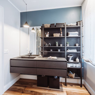 Foto di una stanza da bagno minimal con consolle stile comò, ante in legno bruno, pareti blu, pavimento in legno massello medio, lavabo integrato, pavimento marrone e top marrone