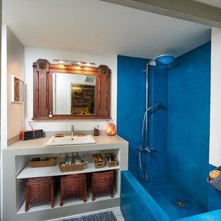 Imagen de cuarto de baño principal, mediterráneo, de tamaño medio, con armarios abiertos, puertas de armario grises, encimera de cemento, encimeras grises, combinación de ducha y bañera, baldosas y/o azulejos azules, paredes blancas y lavabo encastrado