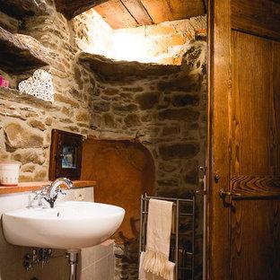 Foto di una piccola stanza da bagno country con pavimento in mattoni, lavabo sospeso e pavimento arancione