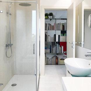 Modelo de cuarto de baño con ducha, contemporáneo, de tamaño medio, con armarios con paneles lisos, puertas de armario blancas, ducha esquinera, sanitario de pared, baldosas y/o azulejos blancos, baldosas y/o azulejos con efecto espejo, paredes blancas, suelo de madera en tonos medios, lavabo sobreencimera, encimera de vidrio, suelo blanco y ducha con puerta con bisagras
