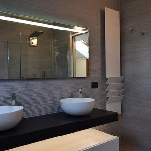 Modelo de cuarto de baño principal, moderno, de tamaño medio, con armarios con paneles lisos, puertas de armario blancas, jacuzzi, ducha esquinera, sanitario de pared, baldosas y/o azulejos grises, baldosas y/o azulejos de porcelana, paredes grises, suelo de baldosas de porcelana, lavabo sobreencimera, encimera de madera, suelo gris, ducha con puerta con bisagras y encimeras marrones