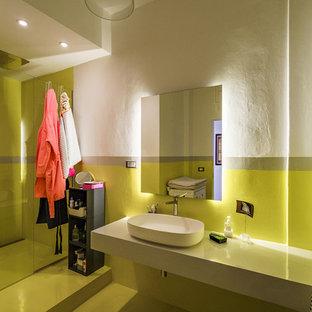 Foto de cuarto de baño con ducha, moderno, grande, con armarios abiertos, puertas de armario grises, ducha a ras de suelo, sanitario de pared, paredes amarillas, suelo vinílico, lavabo sobreencimera, encimera de cemento, suelo amarillo, ducha con puerta con bisagras y encimeras grises