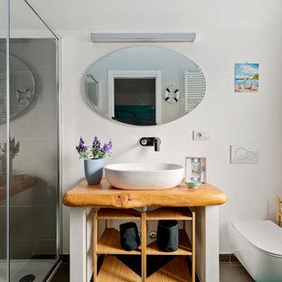 Ispirazione per una stanza da bagno con doccia design di medie dimensioni con ante bianche, doccia alcova, WC sospeso, piastrelle grigie, piastrelle in gres porcellanato, pareti bianche, lavabo a bacinella, top in legno, pavimento marrone, porta doccia scorrevole e top beige