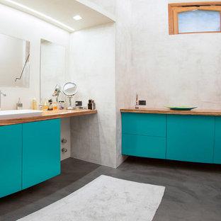 Foto de cuarto de baño principal, bohemio, de tamaño medio, con armarios con paneles lisos, puertas de armario turquesas y encimera de madera