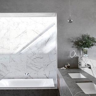 Immagine di una grande stanza da bagno padronale etnica con vasca da incasso, pareti grigie, pavimento in marmo, lavabo integrato e top in marmo