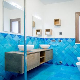 Immagine di una stanza da bagno stile marino con ante lisce, ante in legno scuro, doccia ad angolo, WC sospeso, pareti bianche, lavabo a bacinella, top in legno, pavimento blu, porta doccia a battente e top marrone