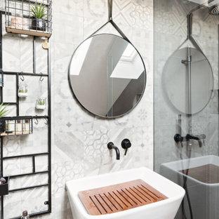Foto di una stanza da bagno design con piastrelle grigie e lavabo sospeso