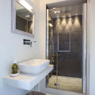 Ispirazione per una stanza da bagno contemporanea con pareti bianche, pavimento in gres porcellanato, lavabo a bacinella, doccia alcova, piastrelle nere e porta doccia a battente