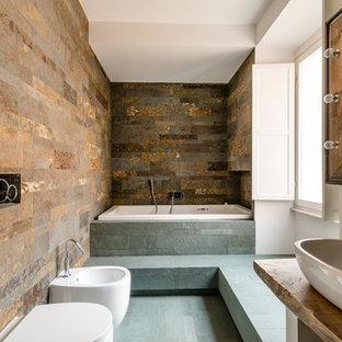 Diseño de cuarto de baño principal, rústico, con puertas de armario de madera clara, bañera encastrada, bidé, paredes marrones, lavabo sobreencimera y encimera de madera
