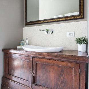 Immagine di una stanza da bagno chic con ante in legno bruno e top in legno
