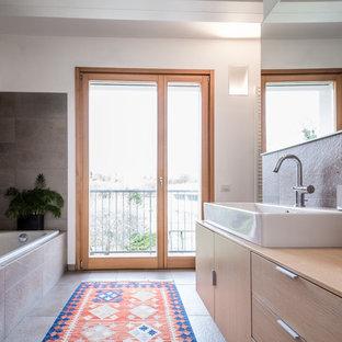 Ispirazione per una stanza da bagno padronale contemporanea di medie dimensioni con ante lisce, ante in legno chiaro, vasca da incasso, piastrelle grigie, pareti bianche, lavabo a bacinella, top in legno e pavimento grigio