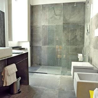Immagine di una grande stanza da bagno con doccia design con nessun'anta, ante grigie, doccia a filo pavimento, piastrelle grigie, piastrelle in gres porcellanato, pareti bianche, pavimento in gres porcellanato, lavabo rettangolare e top in acciaio inossidabile