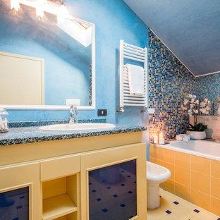 Cette image montre une salle d'eau marine avec un placard à porte shaker, des portes de placard jaunes, une baignoire en alcôve, un carrelage bleu, un carrelage jaune, carrelage en mosaïque, un mur bleu, un lavabo posé, un sol jaune et un plan de toilette noir.