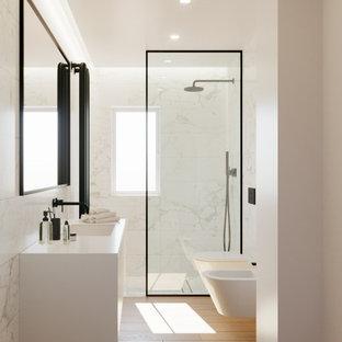 Идея дизайна: ванная комната среднего размера в современном стиле с фасадами с декоративным кантом, белыми фасадами, душем без бортиков, биде, черно-белой плиткой, керамогранитной плиткой, полом из керамогранита, душевой кабиной, накладной раковиной, столешницей из ламината, открытым душем, белой столешницей, тумбой под одну раковину, подвесной тумбой и многоуровневым потолком