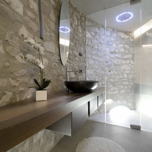 Photo of a small mediterranean ensuite bathroom in Other with a built-in shower, concrete flooring, a vessel sink, wooden worktops, grey floors, a hinged door, brown cabinets and a wall mounted toilet.