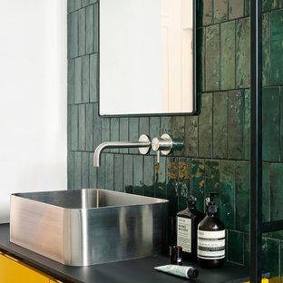 Modelo de cuarto de baño con ducha, minimalista, grande, con armarios con rebordes decorativos, puertas de armario amarillas, ducha abierta, sanitario de pared, baldosas y/o azulejos verdes, baldosas y/o azulejos de cerámica, paredes verdes, suelo de mármol, lavabo sobreencimera, encimera de laminado, suelo gris y encimeras negras