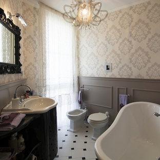 Esempio di una piccola stanza da bagno minimal con nessun'anta, ante nere, pavimento con piastrelle in ceramica, top in vetro, vasca freestanding, bidè, pareti multicolore e lavabo integrato