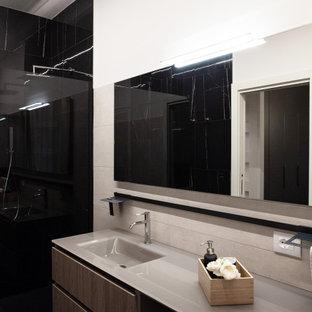 ミラノの中くらいのモダンスタイルのおしゃれなバスルーム (浴槽なし) (落し込みパネル扉のキャビネット、中間色木目調キャビネット、バリアフリー、分離型トイレ、モノトーンのタイル、大理石タイル、ベージュの壁、磁器タイルの床、コンソール型シンク、ガラスの洗面台、オープンシャワー、ベージュのカウンター、黒い床) の写真