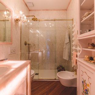 Ispirazione per una stanza da bagno padronale classica di medie dimensioni con nessun'anta, doccia a filo pavimento, WC sospeso, piastrelle di marmo, pareti rosa, parquet scuro, lavabo a bacinella, top in onice, pavimento marrone, porta doccia scorrevole e top rosa