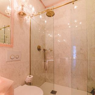 Ispirazione per una stanza da bagno padronale chic di medie dimensioni con nessun'anta, doccia a filo pavimento, WC sospeso, piastrelle di marmo, pareti rosa, parquet scuro, lavabo a bacinella, top in onice, pavimento marrone, porta doccia scorrevole e top rosa
