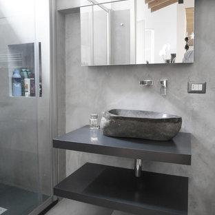 Foto di una stanza da bagno con doccia contemporanea di medie dimensioni con doccia alcova, piastrelle grigie, pareti grigie, pavimento in cemento, lavabo a bacinella, pavimento grigio, porta doccia scorrevole, top grigio e nessun'anta