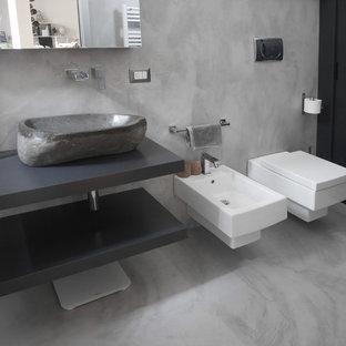 Ispirazione per una stanza da bagno con doccia design di medie dimensioni con ante lisce, ante grigie, doccia alcova, WC sospeso, piastrelle grigie, pareti grigie, pavimento in cemento, lavabo a bacinella, top in legno, pavimento grigio, porta doccia scorrevole e top grigio