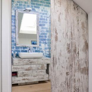 Esempio di una piccola stanza da bagno con doccia shabby-chic style con ante lisce, ante in legno chiaro, doccia ad angolo, WC sospeso, pareti blu, parquet chiaro, lavabo a bacinella e top in laminato