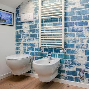 Foto di una piccola stanza da bagno con doccia contemporanea con ante lisce, ante in legno chiaro, doccia ad angolo, WC sospeso, pareti blu, parquet chiaro, lavabo a bacinella e top in laminato