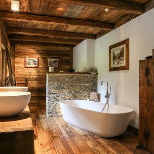 На фото: большие главные ванные комнаты в стиле рустика с плоскими фасадами, отдельно стоящей ванной, паркетным полом среднего тона, настольной раковиной, темными деревянными фасадами, коричневыми стенами, столешницей из дерева, коричневым полом и коричневой столешницей