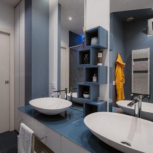 Immagine di una piccola stanza da bagno con doccia minimalista con ante lisce, ante turchesi, doccia alcova, WC a due pezzi, piastrelle blu, piastrelle in gres porcellanato, pareti multicolore, pavimento in gres porcellanato, lavabo a bacinella, top in vetro, pavimento blu, porta doccia scorrevole e top blu