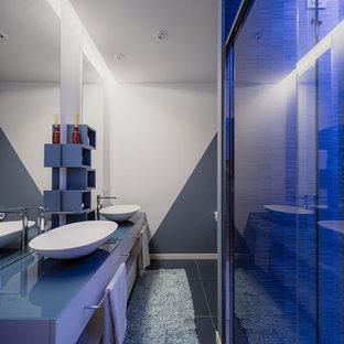 Foto di una piccola stanza da bagno con doccia moderna con ante lisce, ante turchesi, doccia alcova, WC a due pezzi, piastrelle blu, piastrelle in gres porcellanato, pareti multicolore, pavimento in gres porcellanato, lavabo a bacinella, top in vetro, pavimento blu, porta doccia scorrevole e top blu