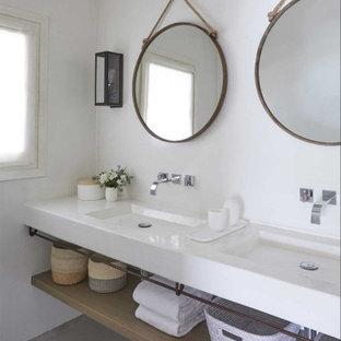 Foto di una stanza da bagno stile marino con pareti bianche, lavabo integrato, pavimento grigio e top bianco