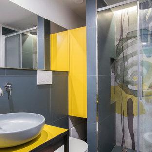Ispirazione per una stanza da bagno con doccia contemporanea con consolle stile comò, ante gialle, WC sospeso, lavabo a bacinella, porta doccia scorrevole, top giallo e pareti grigie