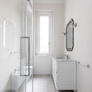Esempio di una stanza da bagno con doccia classica di medie dimensioni con ante bianche, WC sospeso, pareti bianche, lavabo sottopiano, top in marmo e porta doccia scorrevole