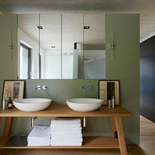 Foto de cuarto de baño contemporáneo, de tamaño medio, con puertas de armario de madera oscura, suelo de madera en tonos medios, lavabo sobreencimera y encimera de madera