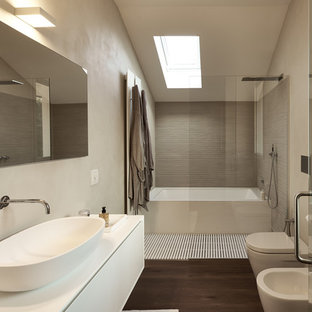 Immagine di una stanza da bagno con doccia contemporanea con ante lisce, ante bianche, vasca ad alcova, doccia a filo pavimento, bidè, pareti grigie, lavabo a bacinella, pavimento marrone e doccia aperta