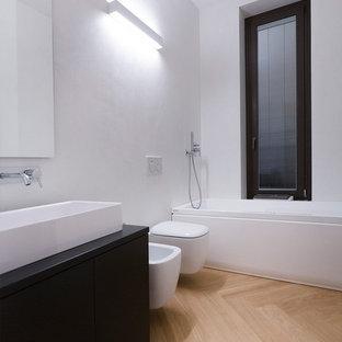Ispirazione per una stanza da bagno moderna di medie dimensioni con ante lisce, ante in legno chiaro, pareti bianche, parquet chiaro, top in legno, pavimento beige, lavabo rettangolare, vasca ad alcova, vasca/doccia, WC monopezzo, piastrelle nere, piastrelle di cemento e doccia aperta