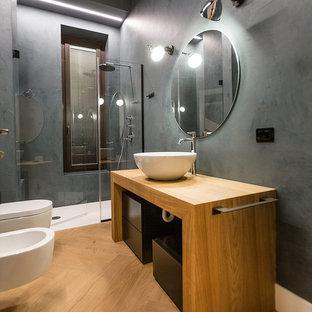 Idee per una stanza da bagno minimalista di medie dimensioni con ante lisce, pareti grigie, parquet chiaro, lavabo a bacinella, top in legno, pavimento beige, ante nere, doccia alcova, bidè, piastrelle nere, piastrelle di cemento e porta doccia a battente