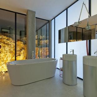 Idee per una grande stanza da bagno padronale minimal con vasca freestanding, pavimento in cemento, lavabo a colonna e ante lisce