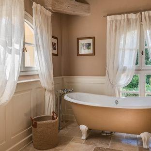 Medelhavsstil inredning av ett stort svart svart badrum med dusch, med luckor med infälld panel, skåp i ljust trä, ett fristående badkar, en kantlös dusch, en toalettstol med separat cisternkåpa, beige väggar, kalkstensgolv, ett undermonterad handfat, marmorbänkskiva, beiget golv och dusch med gångjärnsdörr