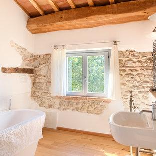 Cette photo montre une salle de bain principale méditerranéenne avec une baignoire indépendante, un carrelage blanc, un mur blanc, un sol en bois clair, un lavabo suspendu, meuble simple vasque et un plafond en bois.