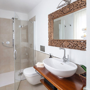 This is an example of a mediterranean bathroom in Cagliari with open cabinets, medium wood cabinets, a built-in shower, a wall mounted toilet, beige tiles, white walls, a vessel sink, wooden worktops, beige floors, a hinged door and brown worktops.