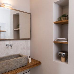 Diseño de cuarto de baño de estilo de casa de campo, grande, con armarios abiertos, puertas de armario de madera en tonos medios, bañera empotrada, sanitario de dos piezas, baldosas y/o azulejos beige, baldosas y/o azulejos de piedra caliza, paredes beige, lavabo de seno grande y encimera de madera
